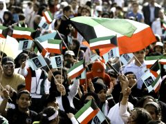 Kuwaitis wave their national flag during celebrations marking the emirate's national and liberation days in Kuwait City on February 20, 2010. National Day commemorates the creation of Kuwait as a nation in 1961 while Liberation Day marks the end of the Iraqi occupation in 1991 during the Gulf War. AFP PHOTO/YASSER AL-ZAYYAT (Photo credit should read YASSER AL-ZAYYAT/AFP/Getty Images)